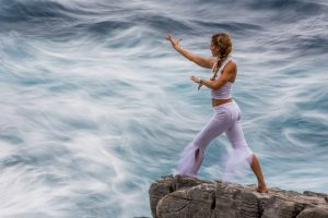Beth Leone doing qigong on the cliffs of Kardamilli, Greece in an oncoming storm
